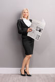 Young blond businesswoman holding a newspaper Royalty Free Stock Photography