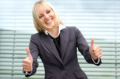 A young blond businesswoman holding thumbs up Royalty Free Stock Image