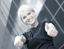 A young blond businesswoman holding thumbs up Stock Photo