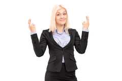 Young blond businesswoman posing with fingers crossed for luck Royalty Free Stock Photography