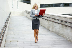 A young blond businesswoman walking with a laptop Stock Photography