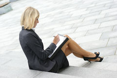 A young blond businesswoman is working outdoors Stock Images