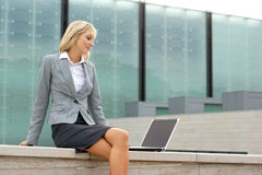 A young blond businesswoman working outdoors Stock Images