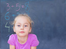 Young blond caucasian girl in front of blackboard Royalty Free Stock Photos