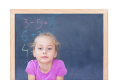 Young blond caucasian girl in front of blackboard Royalty Free Stock Image