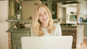 Serious blond woman typing on her laptop stock video footage