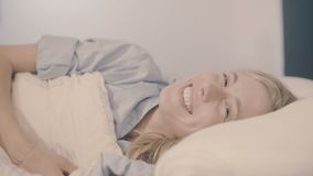 Young woman in bed waking up smiling and stretching looking at the camera stock video