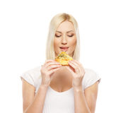 A young blond Caucasian woman eating a hamburger Stock Images