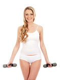 A young blond Caucasian woman holding dumbbells Stock Photography