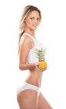 A young blond Caucasian woman holding a pineapple Stock Images