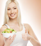 A young blond Caucasian woman holding a salad Royalty Free Stock Images