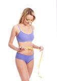 A young blond Caucasian woman measuring her waist Royalty Free Stock Photo