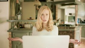 Young woman looking at her laptop shocked by what she sees stock video