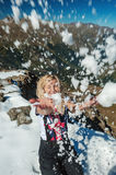 Young blond caucasian woman throwing snow. In the Caucasus mountains, Dombay and laughs Royalty Free Stock Image