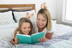 Young blond Caucasian mother lying on bed with her young sweet  7 years old daughter reading book together at home bedroom. Young blond Caucasian women lying on Stock Photography