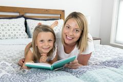 Young blond Caucasian mother lying on bed with her young sweet  7 years old daughter reading book together at home bedroom. Young blond Caucasian women lying on Royalty Free Stock Images