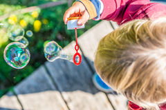 Young blond child blowing bubbles Royalty Free Stock Photos