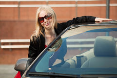 Young blond with a convertible. Royalty Free Stock Photo