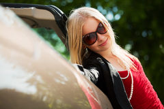Young blond with a convertible Stock Images