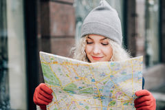 Young blond curly beautiful female tourist. Young blond curly female tourist in warm hat and red gloves with London map looking for a way, winter stock image