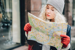 Young blond curly female tourist with map. Young blond curly female tourist in warm clothes and red gloves with London map looking for a way im winter city stock photo
