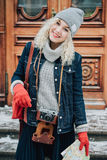 Young blond curly female tourist with old film camera, winter Royalty Free Stock Photos
