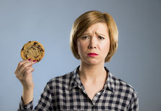 Young blond cute and friendly caucasian woman in casual clothes holding big delicious chocolate cookie. Looking sad in temptation as thinking if ignoring diet Stock Photography