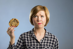 Young blond cute and friendly caucasian woman in casual clothes holding big delicious chocolate cookie. Looking sad in temptation as thinking if ignoring diet Royalty Free Stock Photography