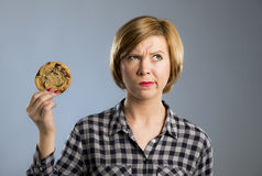 Young blond cute and friendly caucasian woman in casual clothes holding big delicious chocolate cookie. Looking sad in temptation as thinking if ignoring diet Stock Images
