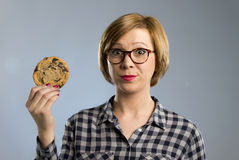 Young blond cute and friendly caucasian woman in casual clothes holding big delicious chocolate cookie. Looking with temptation as thinking if ignoring diet and Stock Image