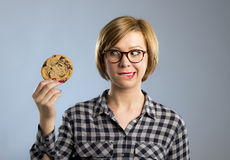 Young blond cute and friendly caucasian woman in casual clothes holding big delicious chocolate cookie Stock Photos