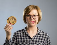 Young blond cute and friendly caucasian woman in casual clothes holding big delicious chocolate cookie. Looking with temptation as thinking if ignoring diet and Stock Images