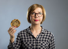 Young blond cute and friendly caucasian woman in casual clothes holding big delicious chocolate cookie. Looking with temptation as thinking if ignoring diet and Royalty Free Stock Photos