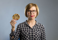 Young blond cute and friendly caucasian woman in casual clothes holding big delicious chocolate cookie. Looking with temptation as thinking if ignoring diet and Royalty Free Stock Image