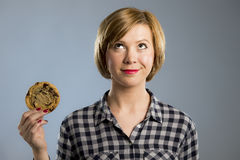 Young blond cute and friendly caucasian woman in casual clothes holding big delicious chocolate cookie. Looking with temptation as thinking if ignoring diet and Royalty Free Stock Photo