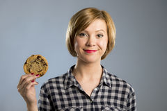 Young blond cute and friendly caucasian woman in casual clothes holding big delicious chocolate cookie. Looking with temptation as thinking if ignoring diet and Stock Photos