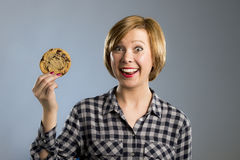 Young blond cute and friendly caucasian woman in casual clothes holding big delicious chocolate cookie. Looking with temptation as thinking if ignoring diet and Stock Photo