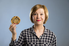Young blond cute and friendly caucasian woman in casual clothes holding big delicious chocolate cookie. Looking with temptation as thinking if ignoring diet and Stock Photography