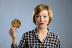 Young blond cute and friendly caucasian woman in casual clothes holding big delicious chocolate cookie. Looking with temptation as thinking if ignoring diet and Royalty Free Stock Photography