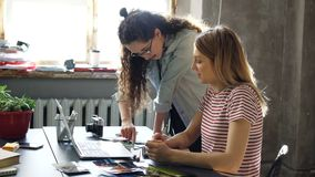 Young designer is drawing images in notebook while her colleague is showing her laptop screen and sharing ideas. Women. Young blond designer is drawing images in stock footage