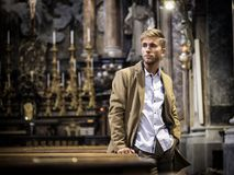 Young man sitting in church. Young blond elegant man sitting in church, on wooden bench, thinking and praying, looking around royalty free stock photos