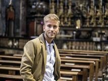 Young man sitting in church. Young blond elegant man sitting in church, on wooden bench, thinking and praying, looking around royalty free stock photo