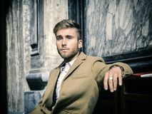 Young man sitting in church. Young blond elegant man sitting in church, on wooden bench, thinking and praying, looking around stock images