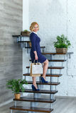 Young blond elegant woman with shopping bags on the stairs Royalty Free Stock Image
