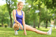 Young blond female exercising in a park. On sunny day Royalty Free Stock Photo