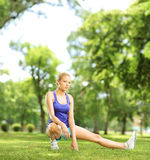 Young blond female exercising in a park on a sunny day. Shot with a tilt and shift lens Stock Photography