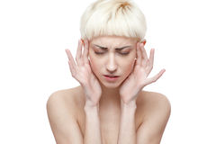 Young blond female has a headache. Horizontal beauty portrait of young attractive blond caucasian female which close her eyes and holding hands near her head Royalty Free Stock Photo