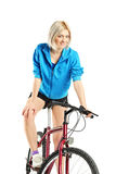 Young blond female posing on a bicycle Royalty Free Stock Image