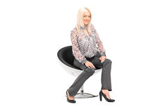 Young blond female sitting on a chair Royalty Free Stock Image