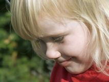 Young blond girl. Is looking concentrated Royalty Free Stock Image